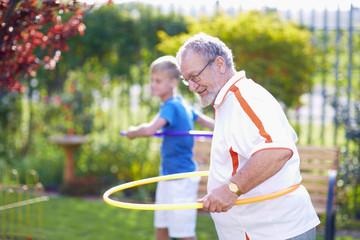 Großeltern mit Enkel im Park, üben mit Hula Hoops