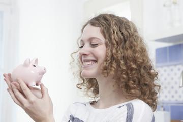 Deutschland, Bayern, München, junge Frau mit Sparschwein, lächelnd