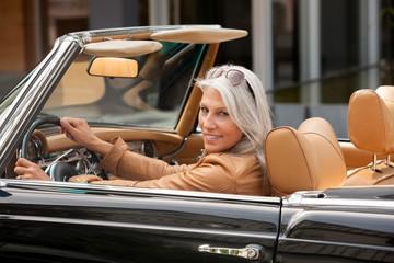 Portrait, ältere Frau sitzt in einem Cabrio