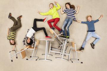 Kinder balancieren auf Schulstühlen