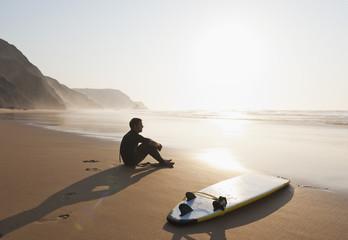 Portugal, Junger Mann sitzt am Strand mit Surfbrett