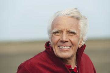 Deutschland, St.Peter-Ording, Nordsee, älterer Mann lächelnd am Strand