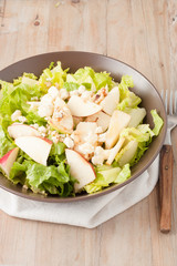 salad with apples and walnuts on rustic wooden background