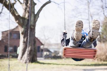 Deutschland, Mecklenburg-Vorpommern, Rügen, kleiner Junge schwingt auf Spielplatz