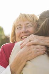 Portrait der glücklichen älteren Frau umarmt Enkelin