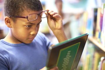 Junge in Bibliothek, mit Tablet-PC