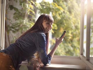 Lächelnde Frau am offenen Fenster mit Handy