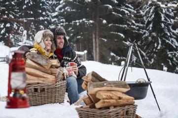 Lächelnde Paare im Schnee mit Brennholz