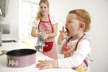 Mutter und kleine Tochter backen Kuchen in ihrer Küche
