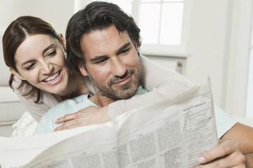 Deutschland, Berlin, Älteres Paar liest Zeitung, lächelnd
