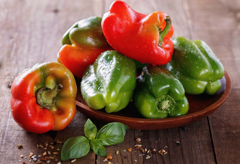 Colorful bell peppers over rustic wooden background