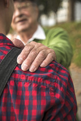 Senior lächelt erwachsenen Enkel an