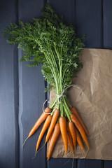 Karotten mit braunem Papier auf Holztisch, close up