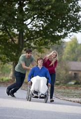 Junges Paar mit Freund im Rollstuhl