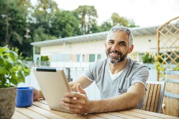 Portrait, Mann mit Tablet-PC auf dem Balkon
