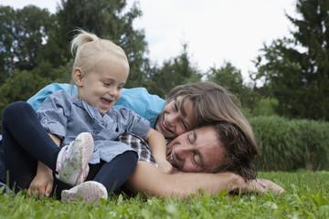 Deutschland, München, Vater mit Kindern im Garten, lächelnd