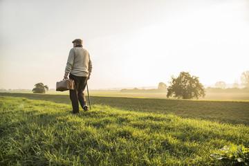 Älterer Mann mit Tasche zu Fuß