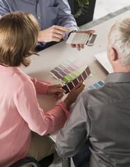 Drei Menschen diskutieren Farbmuster