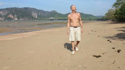 old man of athletic build walks along sand beach against rocky