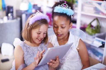 Zwei Mädchen mit Tablet-PC auf einer Geburtstagsparty
