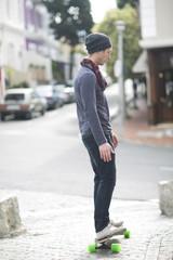 Junger Mann auf seinem Skateboard auf dem Bürgersteig