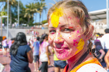 Colorful face of young woman in the indian festival Holi
