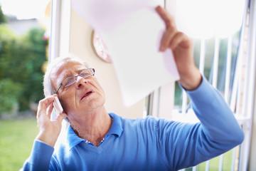 Älterer Mann mit Handy und Dokument