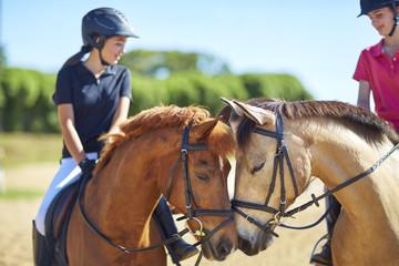 Zwei Mädchen auf Pferden