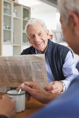 Deutschland, Leipzig, Senior liest Zeitung, ein anderer Mann rührt Kaffee