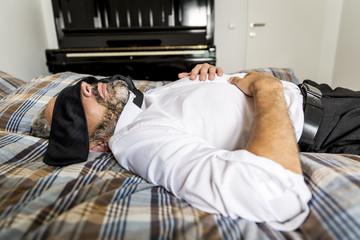 Geschäftsmann auf seinem Bett liegend mit Krawatte auf den Augen