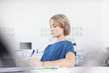 Portrait der nachdenklichen jungen Frau an ihrem Schreibtisch in einem kreativen Büro