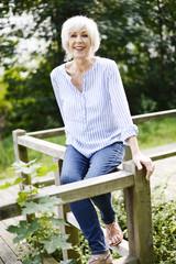 Porträt der lächelnden weißhaarigen Seniorin, sitzt auf hölzernem Geländer