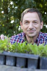 Deutschland, Sachsen, älterer Mann mit Topfpflanze, Lächeln, Portrait