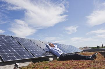 Deutschland, München, älterer Mann ruht auf Panel in Solaranlage, lächelnd