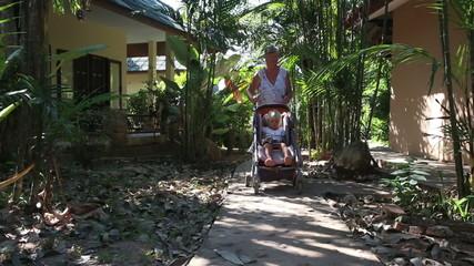 grandmother carries blonde toddler in pram