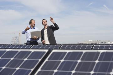 Deutschland, München, Ingenieur und Mann diskutieren in Solaranlage