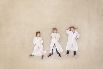 Kinder tragen Laborkittel und forschen