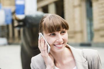 Deutschland, Hessen, Frankfurt am Main, Porträt Telefonierende Geschäftsfrau vor Börse
