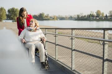 Deutschland, Baden-Württemberg, Mannheim, Enkelin mit Grossmutter im Rollstuhl