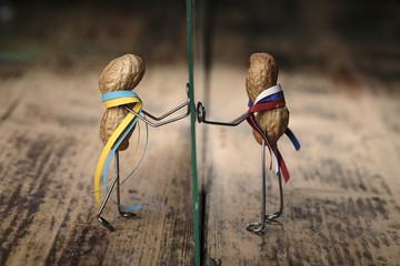 Erdnuss Puppen mit ukrainischen und russischen Nationalfarben durch Glasscheibe getrennt