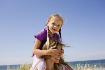 Deutschland, Ostsee, Mutter mit Tochter (6-7) auf Schultern, Portrait
