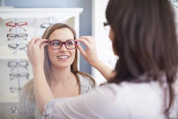 Frau beim Optiker probiert Brillen auf
