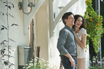 Deutschland, Bayern, Paar am Eingang des Hauses, lächelnd