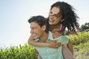 Deutschland, Bayern, Mann mit Frau auf dem Rücken, lächelnd