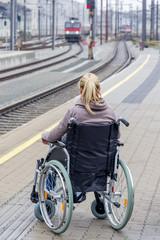 Frau im Rollstuhl wartet am Bahnsteig