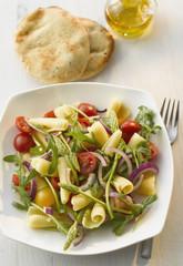 Teller mit Campanelle Salat mit wildem Spargel und Naan auf dem Tisch