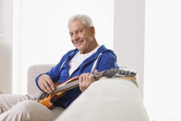 Deutschland, Leipzig, älterer Mann sitzt auf dem Sofa und zupft Gitarre