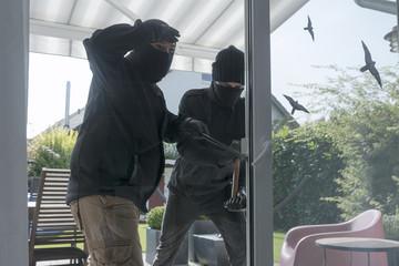 Zwei Einbrecher öffnen Terrassentür eines Einfamilienhauses mit Hammer und Brecheisen tagsüber