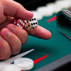 Backgammon player's hand holding the dice square