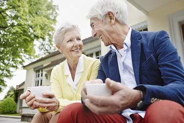 Deutschland, Hessen, Frankfurt am Main, älteres Paar sitzt auf Treppe, Tee trinken